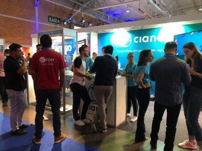 #PraCegoVer na imagem o fundo é o estande Cianet, com parede azul e logotipo.  Em primeiro plano estão em média 13 pessoas conversando.